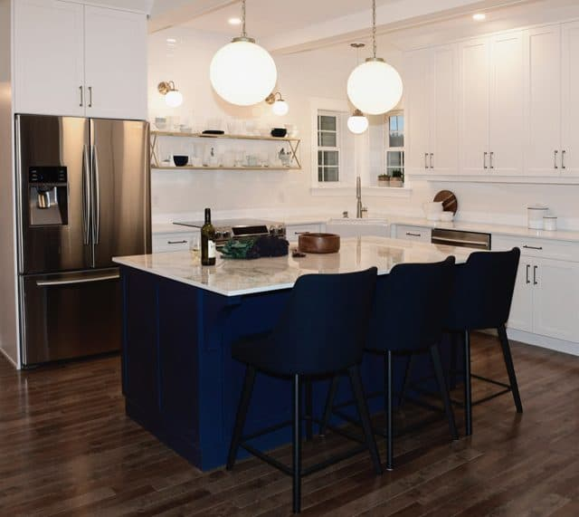 Navy blue kitchen island with globe lights