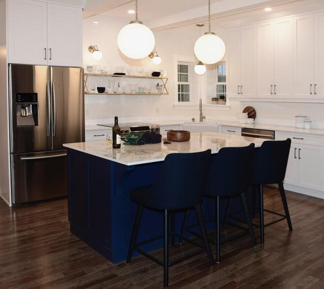 Navy blue kitchen island with globe lights