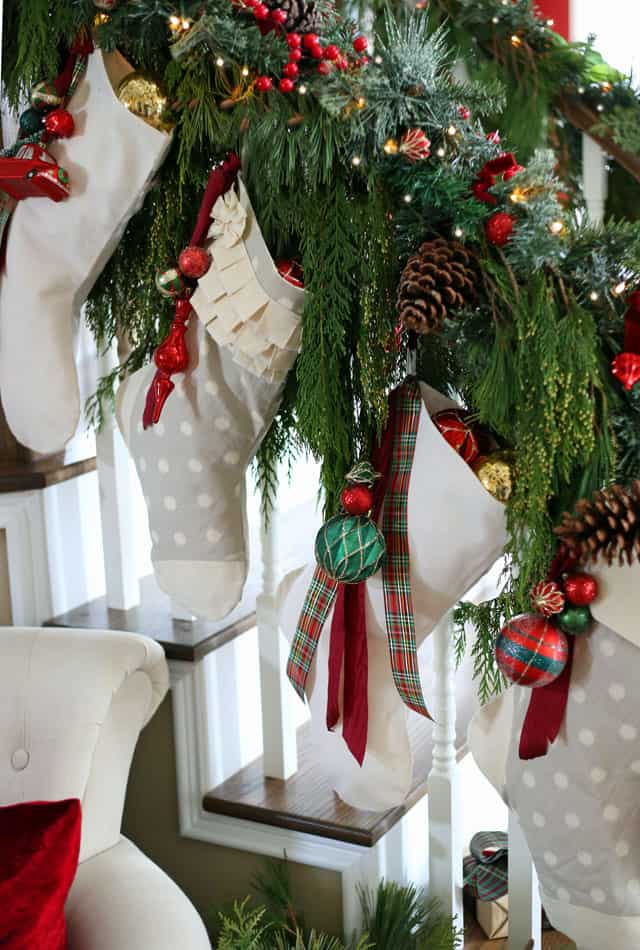 Christmas stockings hung on the banister with natural greenery