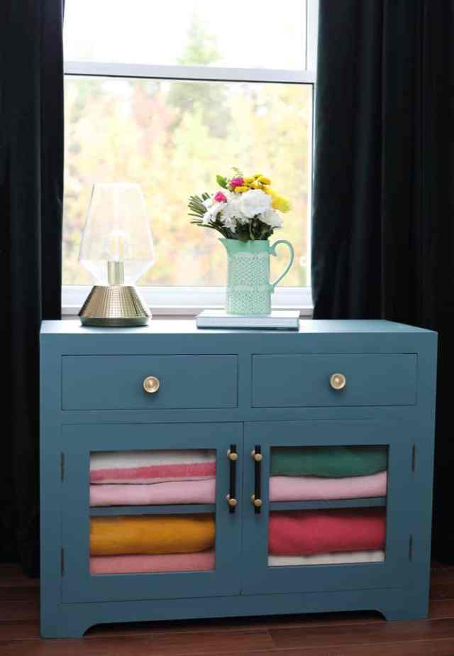 TV stand repurposed as a blanket chest Bright and Colourful Master Bedroom refresh | Colorful Master Bedroom Refresh by popular home decor blog, FYN Designs: image of a bright and colorful master bedroom with a tv stand repurposed as a blanket chest.