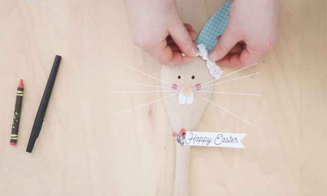 Easter Bunny Crafts: How to Make a Cute Wooden Spoon Easter Bunny, a tutorial featured by top craft blog, Fynes Designs: hot glue a bow on | Easter Bunny Crafts by popular interior design blog, Fynes Designs: image of a woman hot gluing a bow to a wooden spoon Easter Bunny.