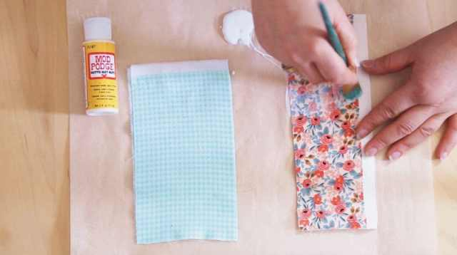 Easter Bunny Crafts: How to Make a Cute Wooden Spoon Easter Bunny, a tutorial featured by top craft blog, Fynes Designs: Paint the fabric scraps with mod podge | Easter Bunny Crafts by popular interior design blog, Fynes Designs: image of a woman apply Mod Podge glue to fabric.