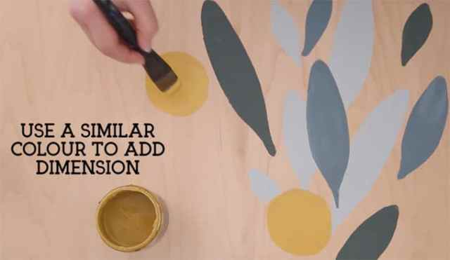 How to paint your own wallpaper mural, a step by step tutorial featured by top life and style blog, Fynes Designs | How to Paint Over Wallpaper in a Bathroom by popular US DIY blog, Fynes Designs: image of a woman painting with a leaf and flower template.
