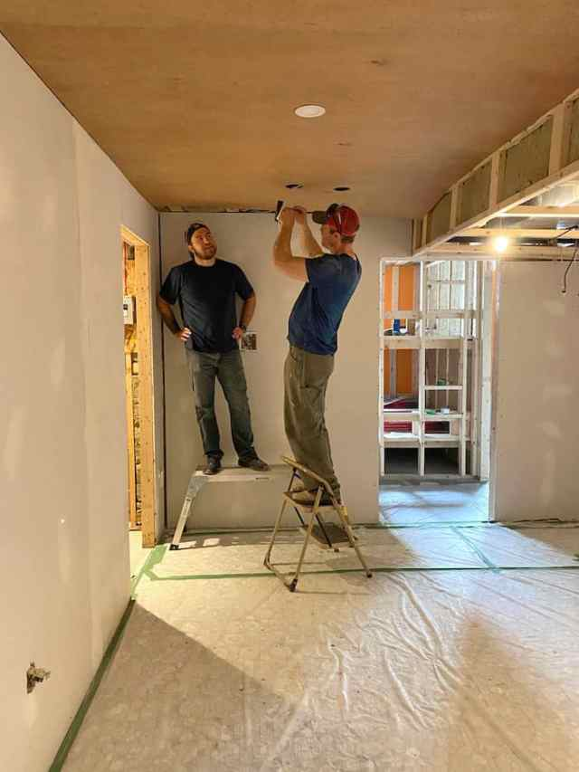 Jeffrey Court by popular US interior design blog, Fynes Designs: image of two men installing canned lighting.