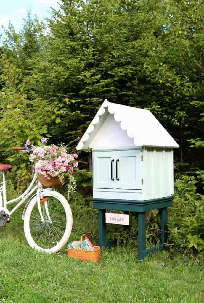 Adorable Free Little Library | Little Free Library Plans by popular US DIY blog, Fynes Designs: image of a free little library next to a beach cruiser bike with a wicker basket full of pink flowers.