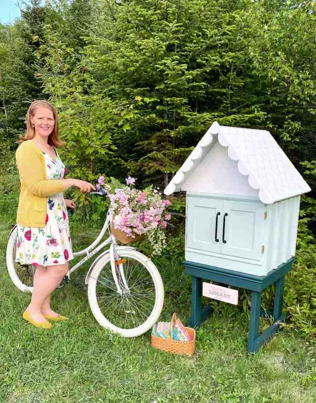Little free library from Fynes Designs | Little Free Library Plans by popular US DIY blog, Fynes Designs: image of a free little library and a woman standing next to a beach cruiser bike with a wicker basket full of pink flowers.