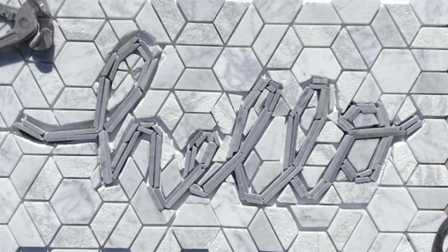 how to cut a word in tile | Tile Lettering by popular US interior design blog, Fynes Designs: image of hello tile lettering being placed on a tile floor.