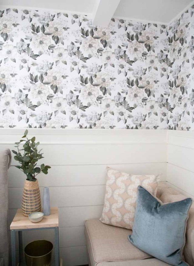 Add charm to basement walls with Shiplap and wallpaper | Master Bedroom Design by popular Canada interior design blog, Fynes Designs: image of a bedroom with floral wall paper, vinyl plank flooring, modern light fixture, tuft bench, and tufted bed frame.
