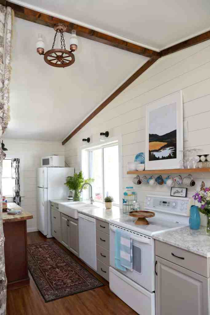 Beautiful shiplap walls in 1980s Farmhouse Cottage makeover |Farmhouse Cottage by popular Canada DIY blog, Fynes Designs: after image of a 1980's farmhouse cottage kitchen with light grey cabinets, chip lap walls, butcher block island, apron sink, and wooden cake stand.