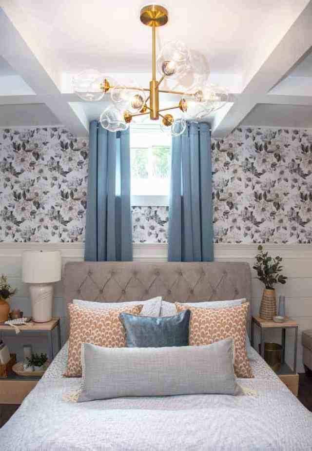 Basement Master Bedroom ideas | Master Bedroom Design by popular Canada interior design blog, Fynes Designs: image of a bedroom with floral wall paper, vinyl plank flooring, modern light fixture, tuft bench, and tufted bed frame.