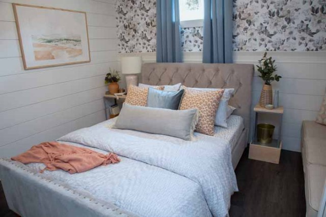 Build a vacation rental in your Basement | Master Bedroom Design by popular Canada interior design blog, Fynes Designs: image of a bedroom with floral wall paper, vinyl plank flooring, modern light fixture, tuft bench, and tufted bed frame.