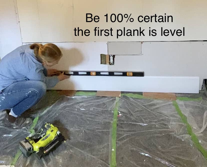 Be certain shiplap is level |Shiplap Wall by popular Canada interior design blog, Fynes Designs: image of a woman making sure her shiplap boards are level.