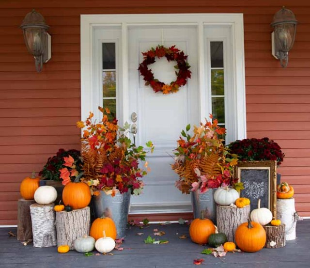 Autumn decorations for your front porch | Fall Front Porch Ideas by popular Canada life and style blog, Fynes Designs: image of a front porch decorated with tree stumps, pumpkins, dark red mums and tin buckets filled with tree branches containing orange, red, and yellow leaves.