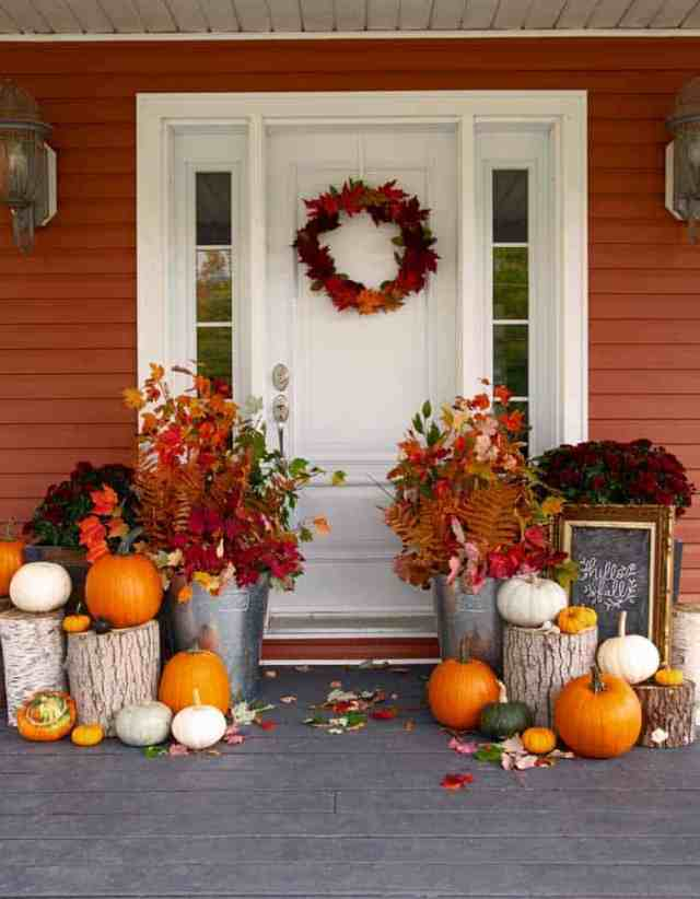 fall front porch decorations | Fall Front Porch Ideas by popular Canada life and style blog, Fynes Designs: image of a front porch decorated with tree stumps, pumpkins, dark red mums and tin buckets filled with tree branches containing orange, red, and yellow leaves.