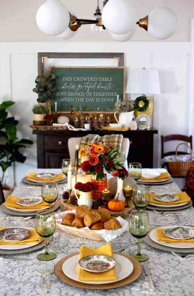 Thanksgiving decor is elevated with a beautiful farmhouse table setting |Thanksgiving decor by popular Canada interior design blog: image of This crowded table chalkboard sign on a dresser decorated with glass bottles, black jars with flowers in them, yellow base lamp, white ceramic pitcher, yellow cloth napkins, faux green plants, and a table set with green wine glasses, white plates, yellow napkins, red and white plates, a basket full of rolls, pinecones, and a vase filled with yellow and red daisies.