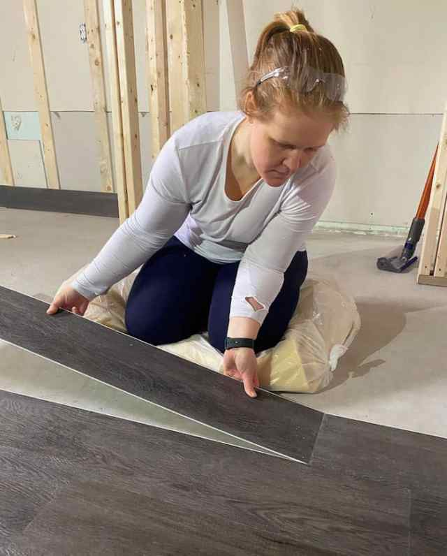How to put flooring down in a basement |Vinyl Plank Flooring by popular Canada interior design blog, Fynes Designs: image of a woman installing vinyl plan flooring in her basement.