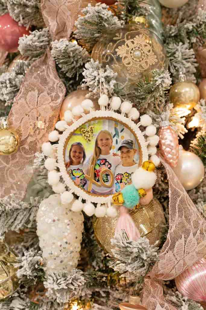IKEA HACK: use a cork coaster to make a sweet photo keepsake ornament |Photo Ornament by popular Canada DIY blog, Fynes Designs: image of a woman holding a photo ornament made from a IKEA coaster and embellished with pom pom ribbon, pom poms, and gold bells.