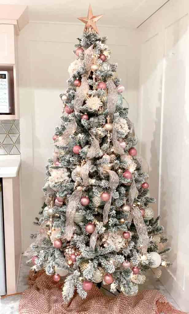 Step by step instructions how to decorate a Christmas tree like a designer |How to Decorate a Christmas Tree with Ribbon by popular Canada DIY blog, Fynes Designs: image of a flocked Christmas tree decorated with pink ribbon and pink, gold, rose gold, light blue and white ornaments.