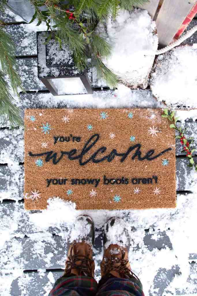 Winter Welcome Mat DIY- FREE SVG |Winter Doormat by popular Canada DIY blog, Fynes Designs: image of a woman standing in front of a winter doormat.