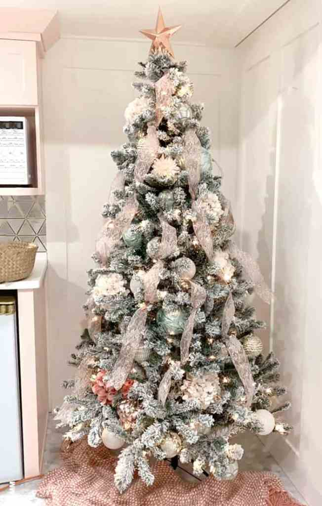 How to put ornaments on a tree like a designer |How to Decorate a Christmas Tree with Ribbon by popular Canada DIY blog, Fynes Designs: image of a flocked Christmas tree decorated with pink ribbon and pink, gold, rose gold, light blue and white ornaments.