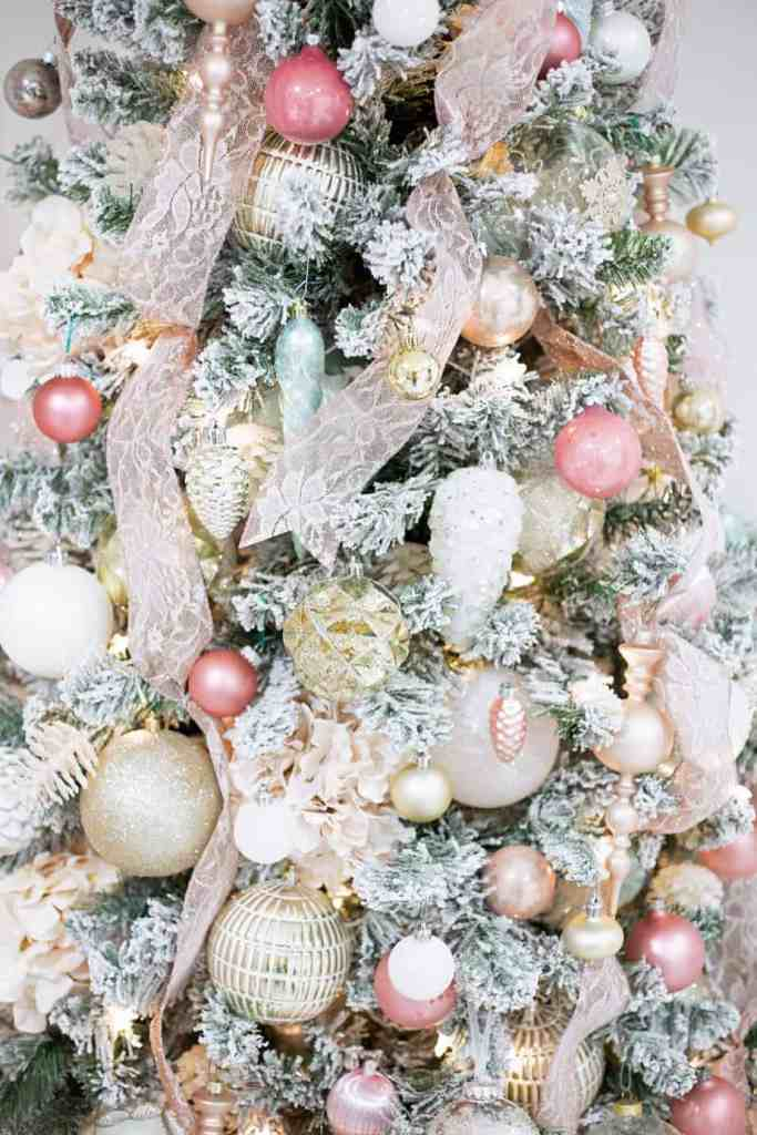 Learn this trick to easily put ribbon on a Christmas tree and save a bundle |How to Decorate a Christmas Tree with Ribbon by popular Canada DIY blog, Fynes Designs: image of a flocked Christmas tree decorated with pink ribbon and pink, gold, rose gold, light blue and white ornaments.