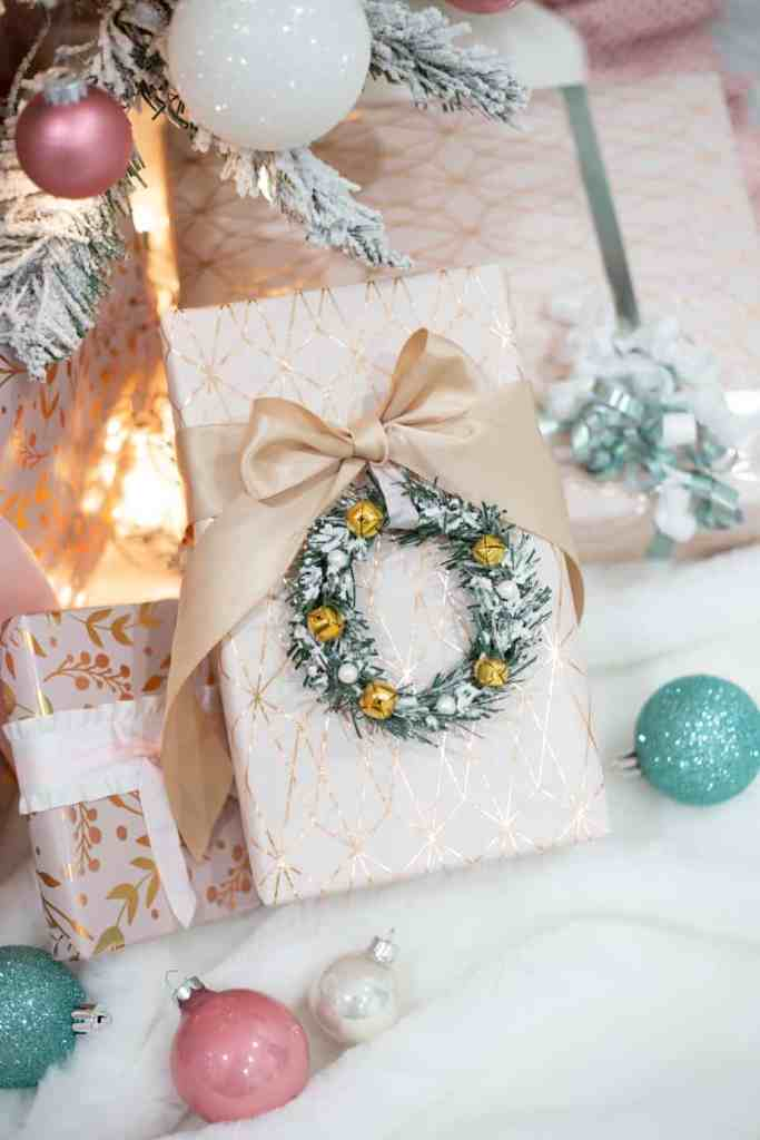 Soft pink and teal Christmas decorations |Colorful Christmas Decorations by popular Canada Interior Design blog, Fynes Designs: image of a present wrapped in gold and white wrapper paper and embellished with a gold ribbon and mini Christmas wreath.