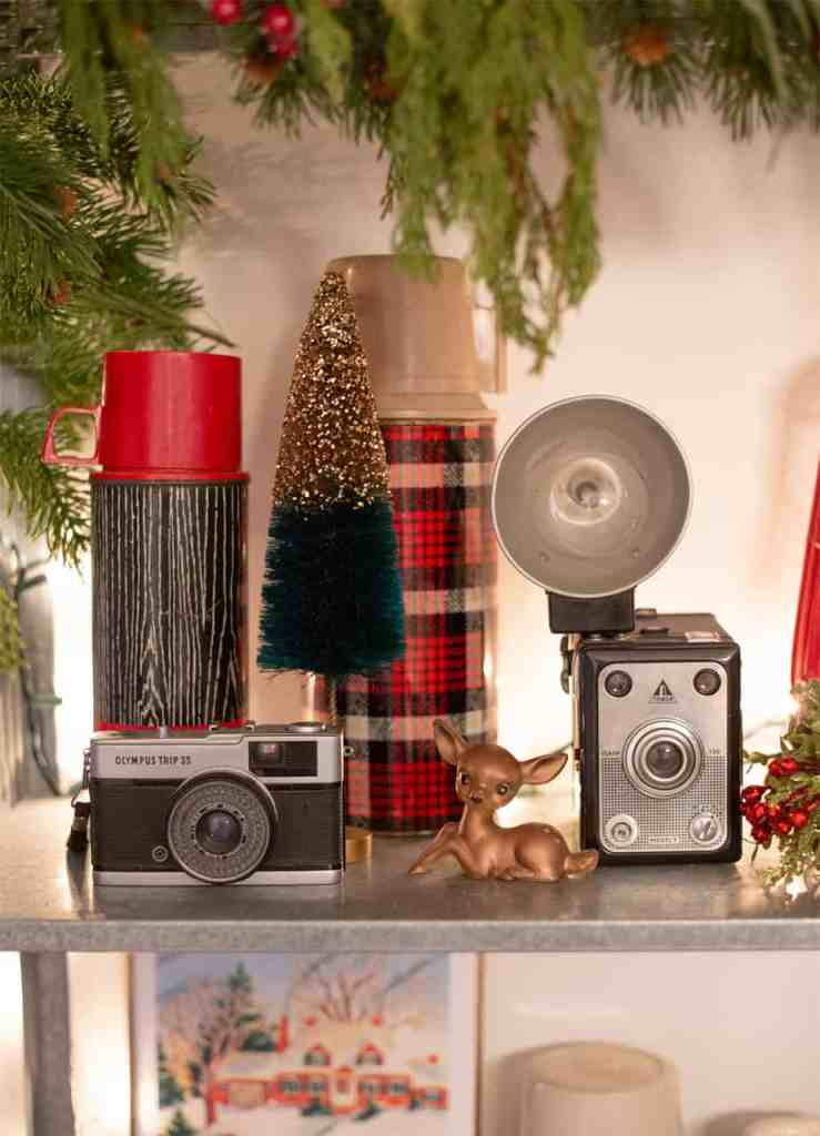 Curated vintage items on a Christmas vignette |How to Hang Garland by popular Canada DIY blog, Fynes Designs: image of a shelf decorated with vintage thermoses, vintage cameras, and a vintage deer.
