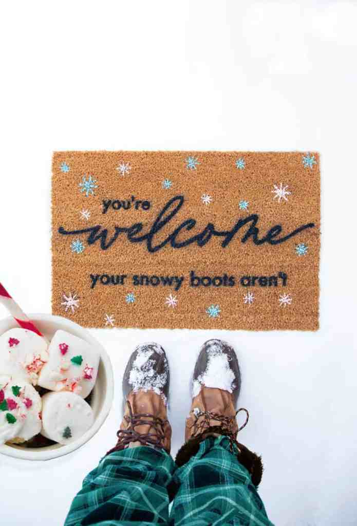 Winter Welcome Mat SVG file | Winter Doormat by popular Canada DIY blog, Fynes Designs: image of a woman holding a mug filled with hot chocolate and marshmallows and standing in front of a winter doormat.
