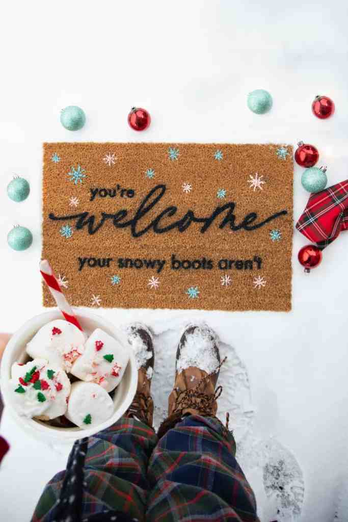 Free Winter SVG for a doormat |Winter Doormat by popular Canada DIY blog, Fynes Designs: image of a woman holding a mug filled with hot chocolate and marshmallows and standing in front of a winter doormat.