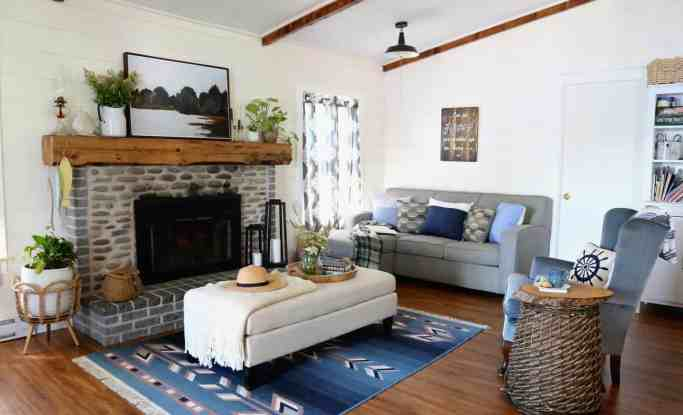 Click to see how a dated 1980s lake house is transformed into a beautiful farmhouse inspired cottage. Must see before and after cottage makeover. |Farmhouse Cottage by popular Canada DIY blog, Fynes Designs: image of a farmhouse cottage living room decorated with blue armchairs, gray sectional couch, black bookshelves, blue accent rug, grey and white curtains, and cream ottoman.
