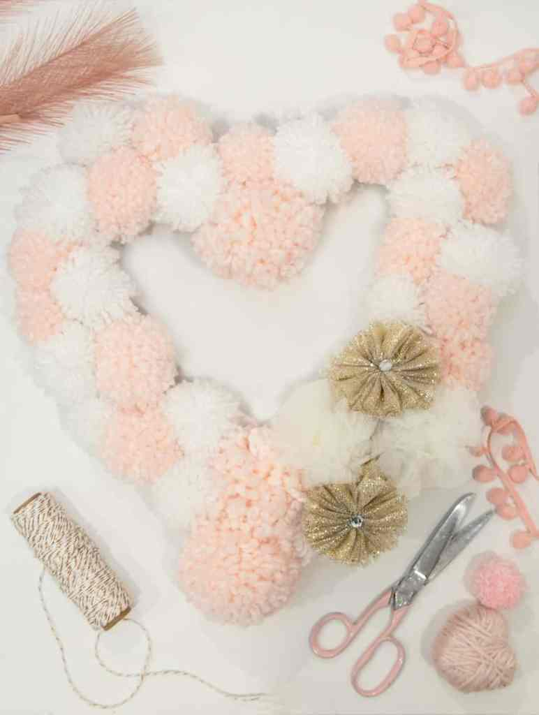 Pom Pom Valentine's wreath tutorial |Heart Shaped Wreath by popular Canada DIY blog, Fynes Designs: Pinterest image of a pink and white heart shaped pom pom wreath.