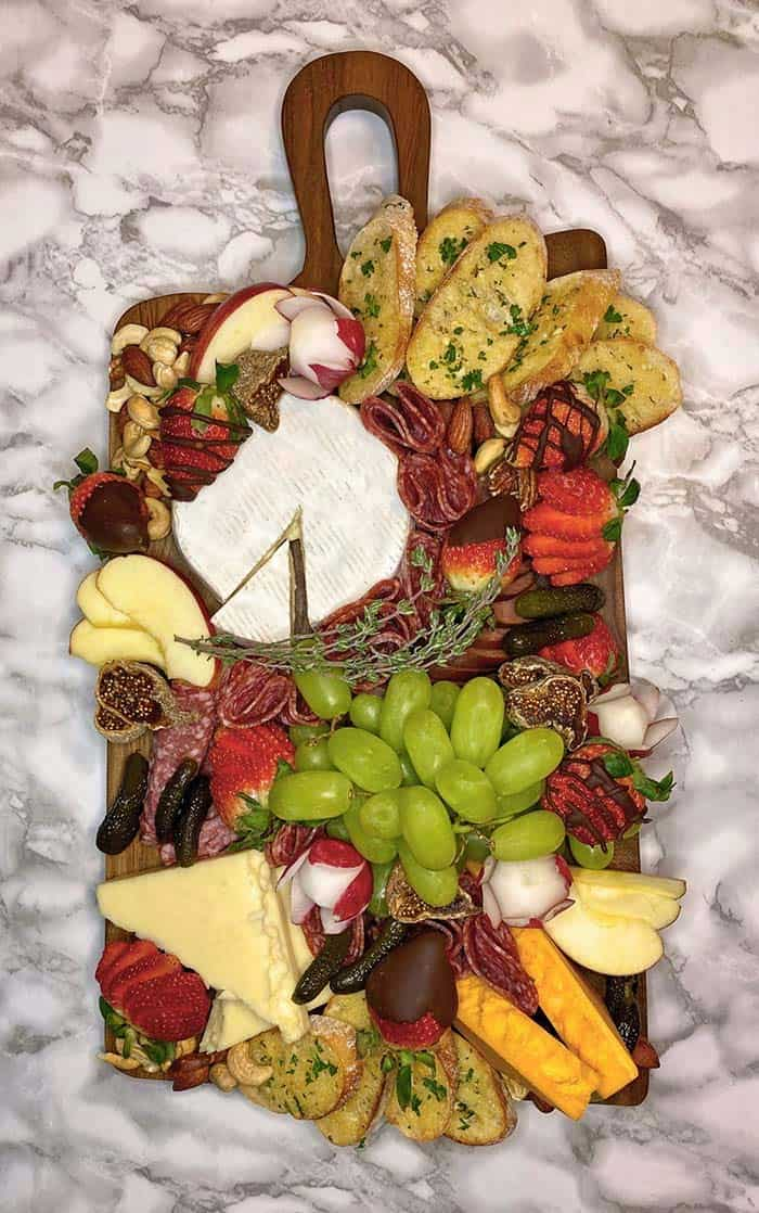 Food garnish and Charcuterie board presentation ideas from a top chef and restaurant owner, Fynes Designs |Charcuterie Board Presentation by popular Canada DIY blog, Fynes Designs: image of a charcuterie board filled with grapes, bread, cheese, crackers, chocolate dipped strawberries, pickles and meat.