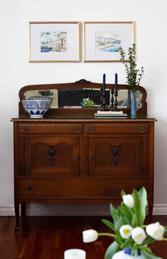 Antique sideboard in a coastal farmhouse inspired living room makeover |Living Room Makeover by popular Canada life and style blog, Fynes Designs: image of a living room with Paris inspired artwork in gold frames hanging above a vintage buffet table.