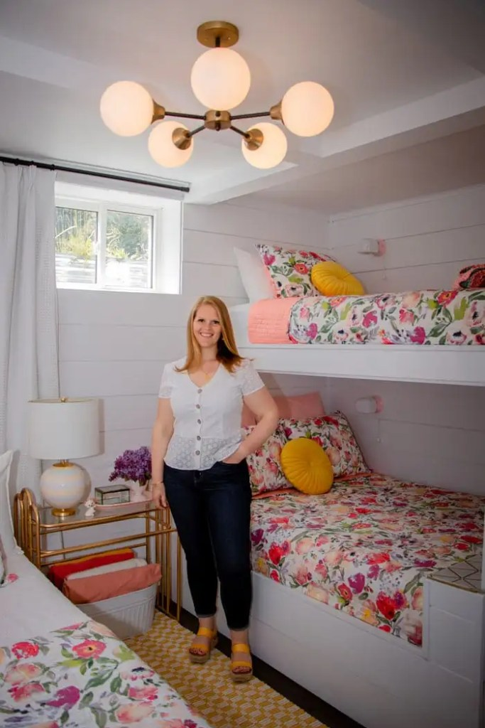 Basement bunk room ideas from designer Virginia Fynes of Fynes Designs |  Bunk Room Ideas by popular Canada home design blog, Fynes Designs: image of a basement bunk room with white shiplap wall, mid century modern chandelier, bunk beds with floral bedding, white drapes, queen bed with a pink headboard and white and floral bedding, yellow and white checked runner rug and a gold metal and glass top side table with a white basket filled with blankets resting underneath.
