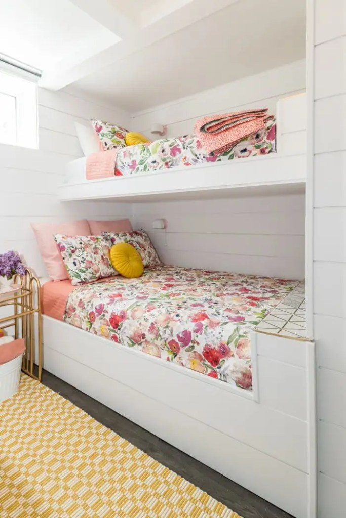 Basement bunk room ideas from designer Virginia Fynes | Bunk Room Ideas by popular Canada home design blog, Fynes Designs: image of a basement bunk room with white shiplap wall, mid century modern chandelier, bunk beds with floral bedding, white drapes, queen bed with a pink headboard and white and floral bedding, yellow and white checked runner rug and a gold metal and glass top side table with a white basket filled with blankets resting underneath.
