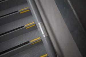 Detalhes em escada - braille no corrimão e faixas de contraste visual e antiderrapante nos degraus.