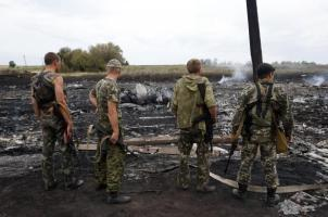 Armed pro-Russian separatists stand at the site of a Malaysia Airlines Boeing 777 plane crash near the settlement of Grabovo in the Donetsk region