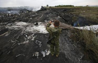 Armed pro-Russian separatist takes pictures at the site of a Malaysia Airlines Boeing 777 plane crash near the settlement of Grabovo in the Donetsk region