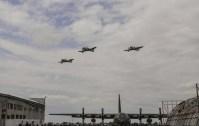 """Hijos de la """"madre de industrias"""", tres IA-58 Pucará de la III Brigada Aérea sobrevuelan FAdeA durante la ceremonia del 90 aniversario. En tierra, el C-130H Hercules TC-61, que se encuentra en pleno proceso de inspección mayor (foto: Fuerza Aérea Argentina)."""