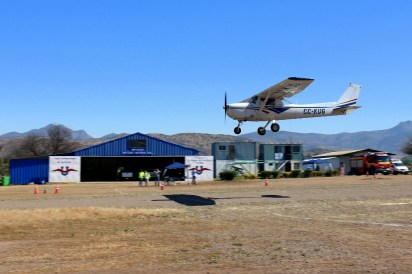 CUA Cessna 150 CC-KUG on a low level pass with club hangar on the background (photo: Carlos Ay).
