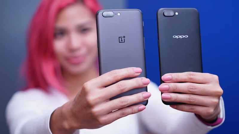 Girl holding the OPPO R11 and the OnePlus 5 side by side