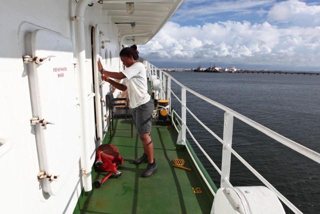 Thuleka Vili tercer oficial de Sudáfrica saca unas mangueras nuevas que reemplazará por las viejas de la embarcación.