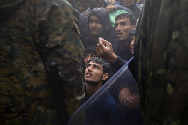 Migrantes y refugiados ruegan a un oficial de policía que les permita el paso para cruzar la frontera de Grecia a Macedonia durante un día de lluvia, cerca de la aldea griega Idomeni. (Yannis Behrakis, Thomson Reuters 10 de septiembre de 2015).