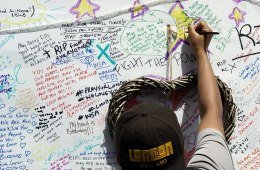 a person wearing a cap writes tributes on a wall remembering those who died in Grenfell Tower fire