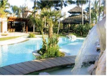 Bali style Infinity pool with waterfall, island, timber bridge and submerged beach