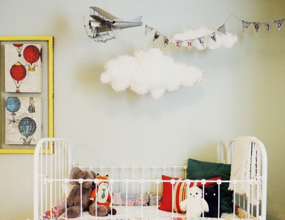 Airplane theme nursery with a hanging airplane with baby's name behind it in a banner. Easy to make