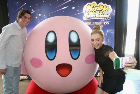 """CULVER CITY, CA - JUNE 22:  In this photo provided by Nintendo of America, Peyton List from Disney's """"Bunk'd' who is starring in the upcoming feature """"The Thinning"""" and Spencer List from """"The Bachelors"""" interact with Kirby at the Kirby: Planet Robobot celebration at Smashbox Studios in Culver City, California, on June 22, 2016. Kirby: Planet Robobot, the latest instalment in the popular franchise, available now for the Nintendo 3DS family of systems.  (Photo by Jonathan Leibson/Getty Images for Nintendo of America) *** Local Caption *** Peyton List;Spencer List"""