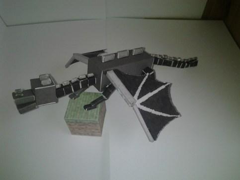 Side view of Enderdragon papercraft on a grass block cutout