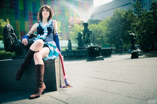 Songstress Yuna Cosplay sitting by water fountain