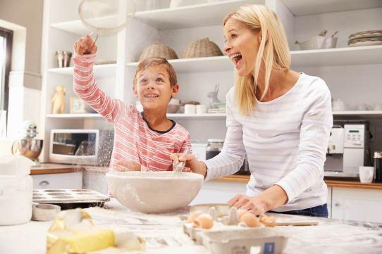 Madre e hijo en la cocina. Están cocinando lo que parece un pastel y están sonrientes.